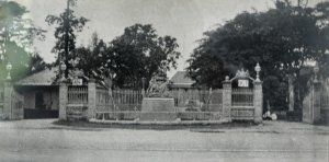 Road entrance to compound, with seated Queen Victoria,1900s.