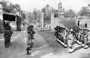 Gurkha guard inside the compound gates, with equestrian statue of Gen. Maude outside, 1940s.