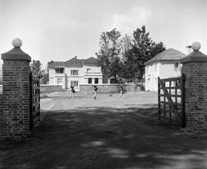 Compound entrance and drive to residence, with offices on the right, 1954.
