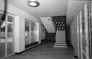 Entrance hall to agency building, with stair up to residence and, at right, door to offices, 1956.